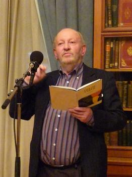 Derek Mahon at a poetry reading with a book in his left hand and a a microphone in the foreground