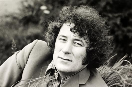 A portrait of Seamus Heaney, with him reclining in a field