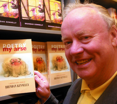 Brendan Kennelly in front of shelves with copies of his books on them
