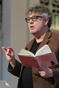 Paul Muldoon with a book in his left hand at a poetry reading